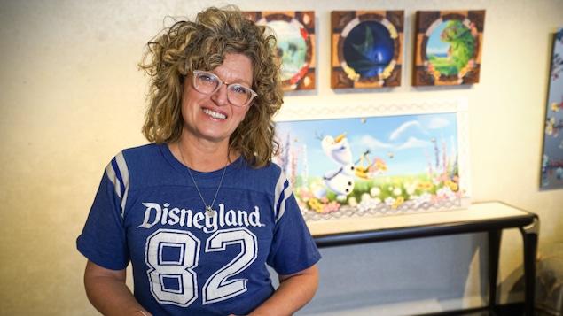 Denyse Klette, souriante, dans son studio avec plusieurs oeuvres accrochées au tableau derrière elle.