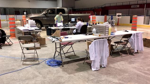 Des travailleuses et travailleurs de la santé avec du matériel médical et le véhicule d'un patient.