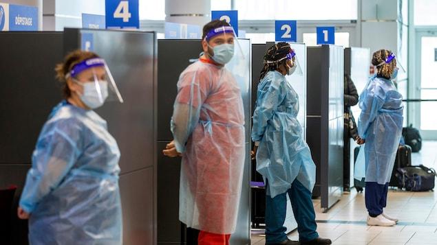 Quatre travailleurs de la santé portant de l'équipement de protection sont debout devant leurs cubicules à l'aéroport.