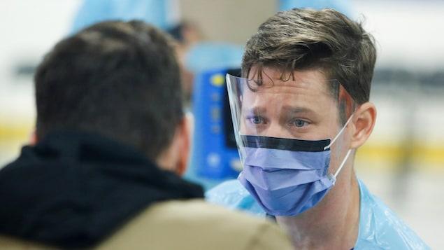 Un médecin effectue un test de dépistage de la COVID-19.