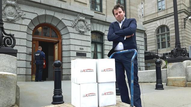Renaud Brossard prend la pose devant l'entrée de l'édifice Honoré-Mercier. Il a les bras croisés et se tient derrière un charriot plat sur lequel ont été déposées les quatre boîtes en carton renfermant les 75 000 signatures recueillies par la pétition de la FCC.