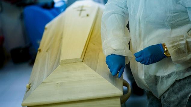 Un employé portant des gants étanches refermant un cercueil.