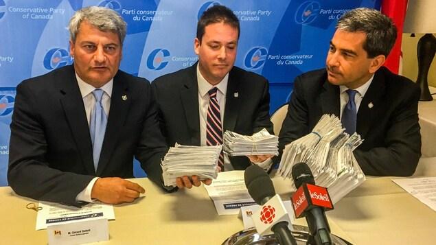 Les députés conservateurs de la région de Québec Gérard Deltell, Alupa Clarke et Pierre Paul-Hus montrent des envois postaux reçus d'électeurs opposés à la légalisation de la marijuana