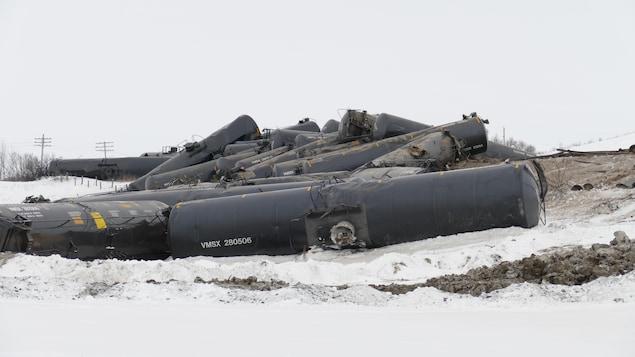 Gros plan sur les wagons de pétrole, empilés les uns sur les autres, dans un champ enneigé.