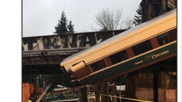 Un wagon de train qui pend d'un viaduc écrase partiellement un autre wagon tombé sur la route.