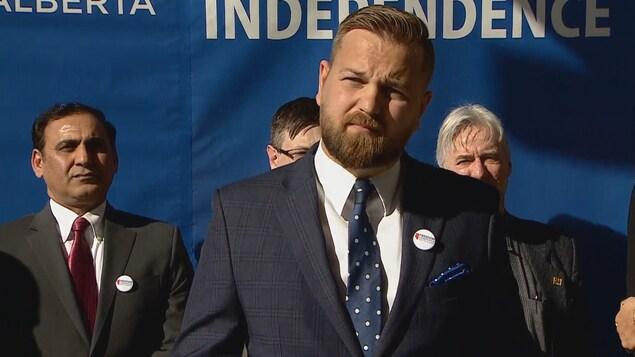 Un homme avec une barbe. Il porte un costard avec une cravate bleue à pois blancs. Trois autres hommes sont situés derrière lui. On aperçoit au fond une banderole qui indique en anglais: « Alberta » et « independence ».