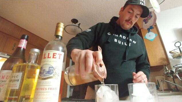 Un homme dans sa cuisine verse un mélangeant alcoolisé dans un verre rempli de glace. Plan vu d'en dessous avec des bouteilles d'alcool sur le comptoir.