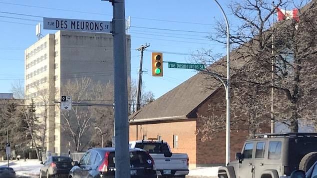 Au bord d'une route, à gauche, un panneau blanc orthographie Des Meurons en deux mots avec une majuscule à Meurons, et à droite un autre panneau vert l'orthographie en un mot.