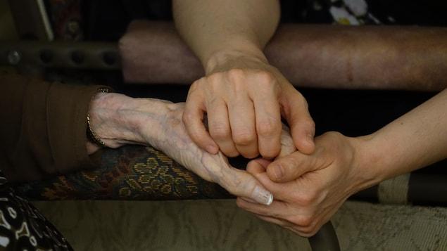 Une intervenante en CHSLD serre la main d'une résidente.
