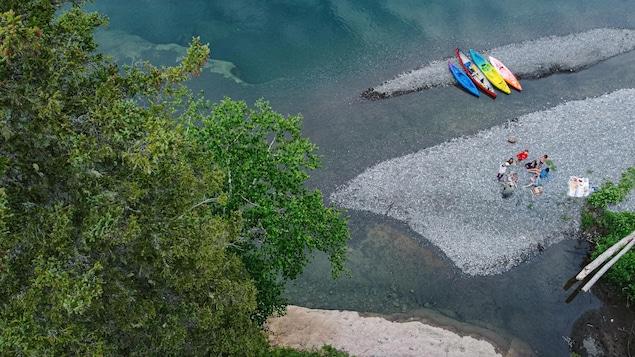 Des usagers de la rivière sont attroupés aux abords du cours d'eau. On aperçoit leurs embarcations derrière eux.