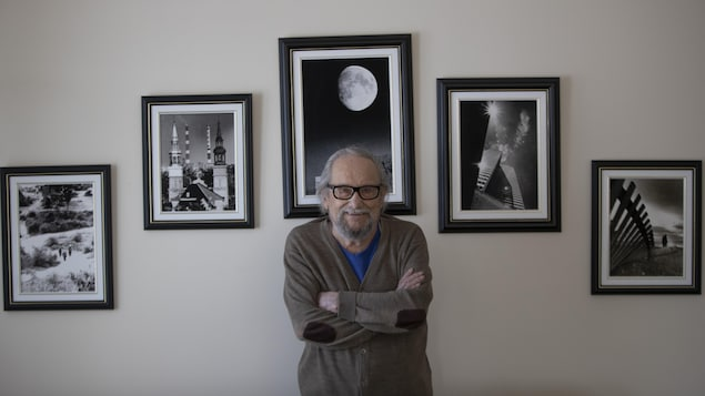 Antoine Désilets, les bras croisés, se tient debout devant des photographies encadrées.