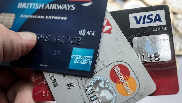 Une personne tient trois cartes de crédit dans sa main.