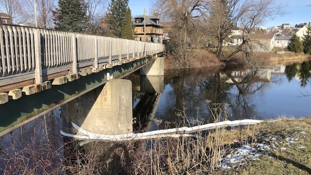 Des remblais tubulaires sont toujours en place sur la rivière, près de la passerelle, pour circonscrire et absorber les hydrocarbures.