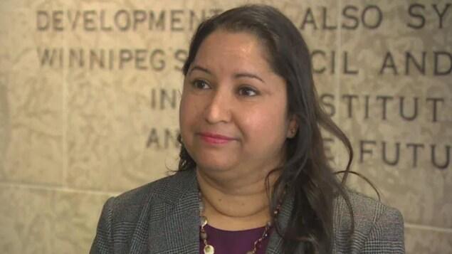 Devi Sharma est vêtue d'un chandail mauve et d'un veston gris. Elle porte un collier.