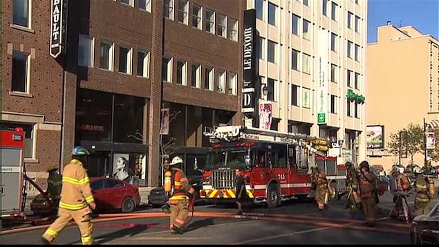 Des pompiers s'affairent à éteindre l'incendie sur le toit du bâtiment qui abrite le journal.