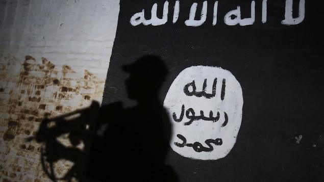 Un membre des forces irakiennes passe devant une murale au logo de Daech dans un tunnel utilisé par les djihadistes dans le village d'Albou Seif, près de Mossoul.
