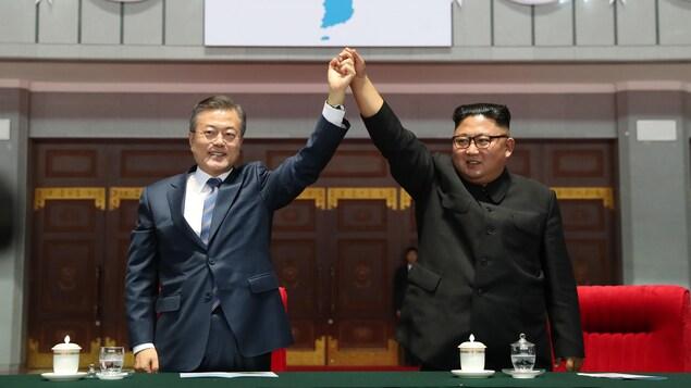 Moon Jae-in et Kim Jong-un lèvent leur bras en se tenant la main.
