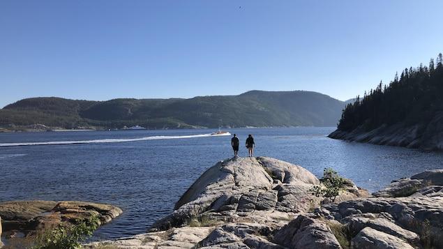 Un couple sur les rochers contemple l'embouchure du fjord du Saguenay