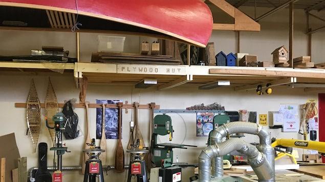 L'atelier de menuiserie à l'école Dennis Franklin Cromarty. On y voit un canot suspendu, des raquettes et des tables de dessin dans une pièce lumineuse.