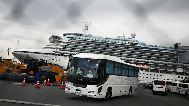 L'autocar est devant le bateau de croisière.