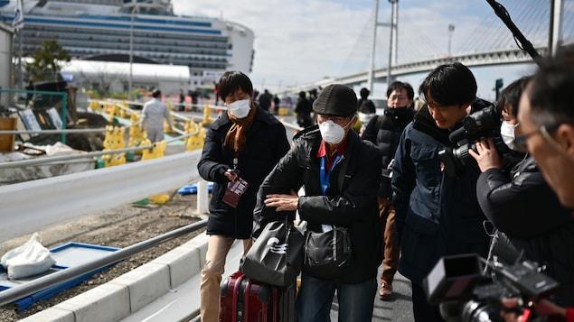 Des journalistes entourent un passager masqué. Le Diamond Princess est visible en arrière-plan.