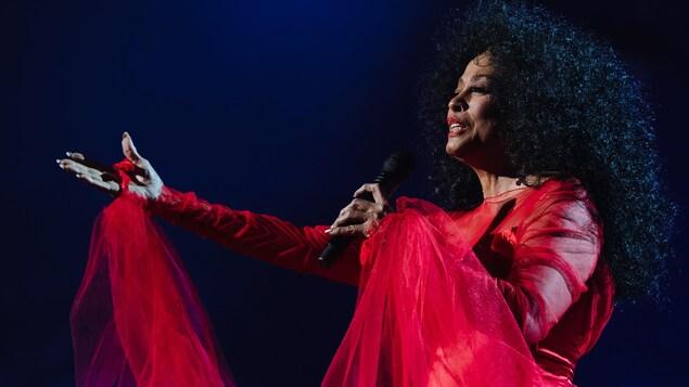 La chanteuse porte une robe rouge et lève le bras en chantant dans un micro sur scène.