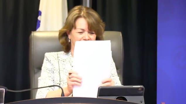 Une capture d'écran de la mairesse Diane Dallaire qui place des feuilles de papier devant elle.
