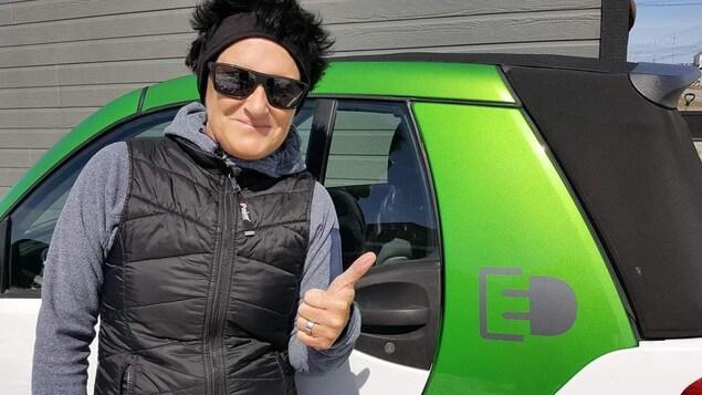 Une femme porte un bandeau sur la tête et des lunettes fumées. Elle est devant un petit véhicule électrique à l'extérieur.