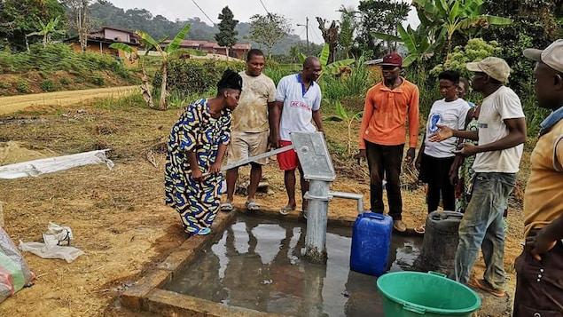 Un groupe de personnes autour d'une fontaine à eau qui fonctionne avec une pompe à actionner.