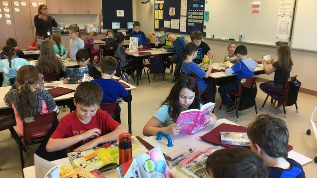 Les élèves assis à leurs pupitres en petits groupes font de la lecture