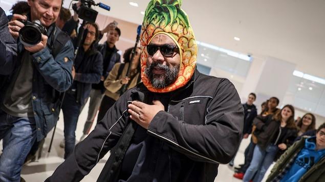 Vêtu de lunettes fumées et d'un couvre-chef en forme d'ananas, l'humoriste Dieudonné fait une «quenelle» devant les caméras à son arrivée dans un tribunal de Paris.
