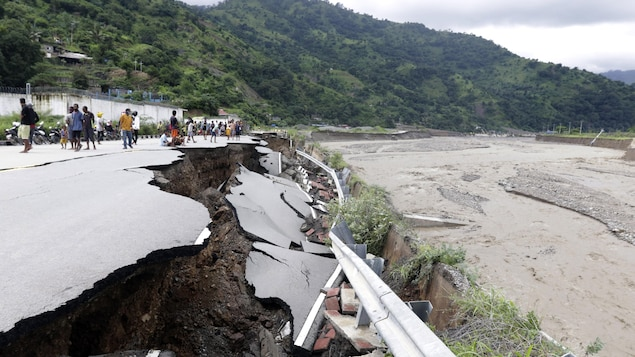 Sur le bord d'un cours d'eau, une route est en grande partie effondrée.