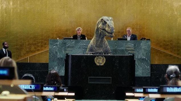 Un dinosaure est à la tribune devant des personnes assises autour de lui.