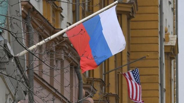 Des drapeaux de la Russie et des États-Unis flottent au vent.