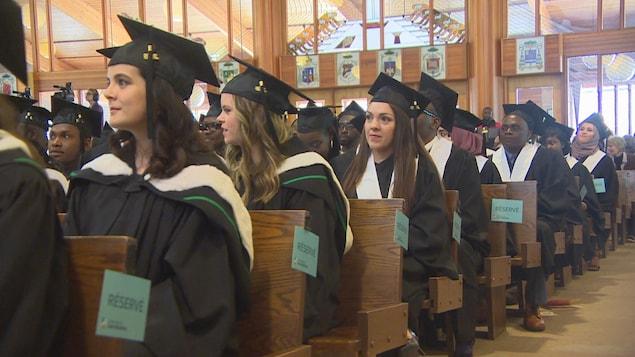 Des étudiants en toge assis lors d'une cérémonie de remise des diplômes.