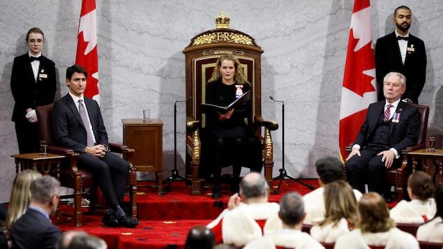 La gouverneure générale, assise sur un trône, tient un cartable dans ses mains. Elle s'adresse notamment à des juges et des élus assis face à elle.