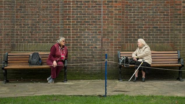 Deux dames âgées font la conversation assises sur deux bancs de parc séparés, à plus de deux mètres de distance l'une de l'autre, le 19 mars 2020 à York, en Angleterre.