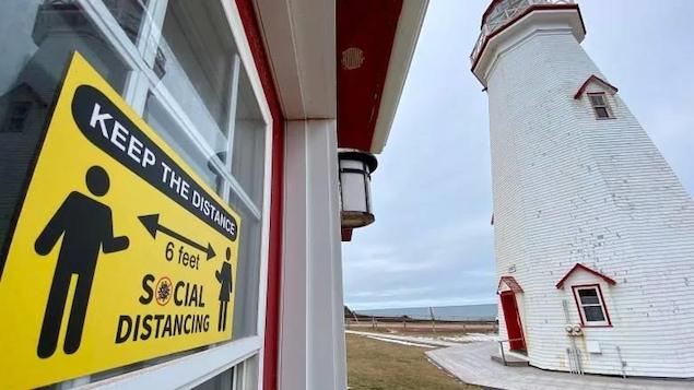 Une affiche qui demande la distanciation sociale près du phare.