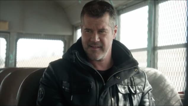 L'homme est assis dans un mini bus et il sourit.