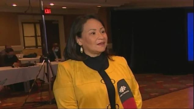Betty Nippi-Albright debout en train de répondre à un journaliste.