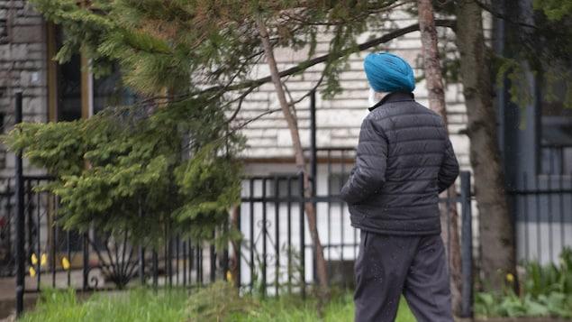 Un homme portant un turban marche dans la rue, les mains dans les poches de son manteau.