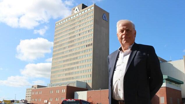 Jim Dixon souriant devant la tour à bureaux haute de 20 étages