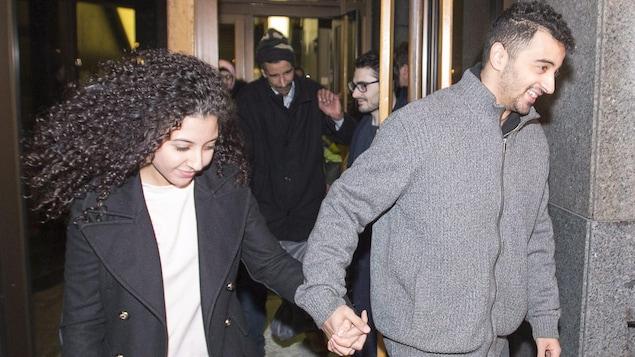 Sabrine Djermane et El Mahdi Jamali se tiennent la main à leur sortie du palais de justice de Montréal.