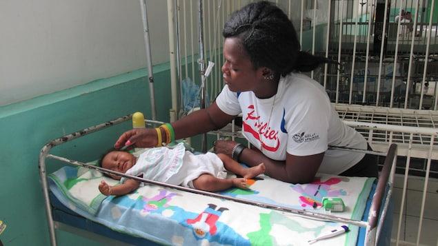 Une mère flatte les cheveux de son bébé, couché sur un lit d'hôpital.