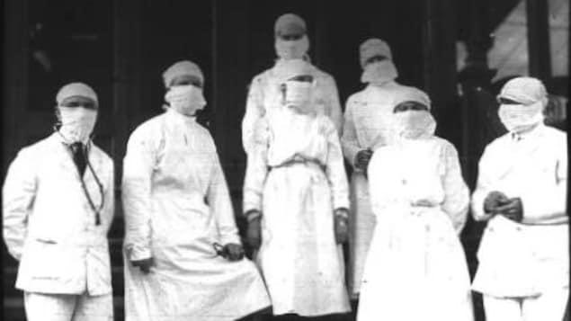 Photo d'époque, six travailleurs de la santé portant un sarrau.