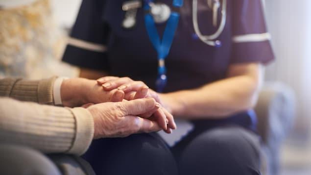 Une infirmière tient la main d'un aîné.