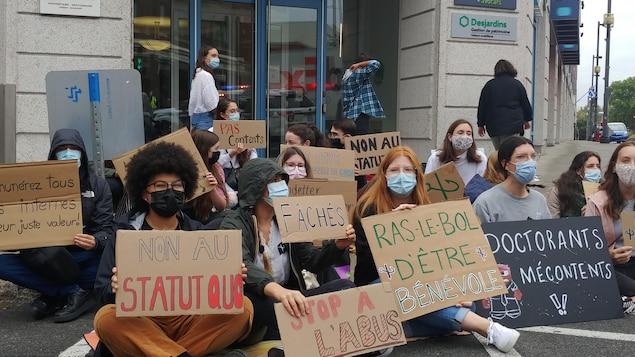 Des étudiants tenant des affiches sont assis sur le sol devant l'entrée de l'édifice Royale abritant le bureau du député de Trois-Rivières.