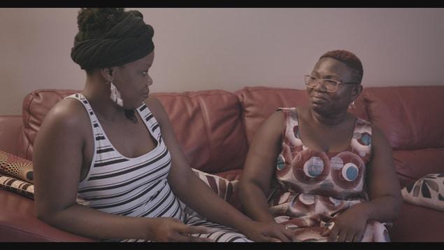 Les deux femmes sont assises l'une à côté de l'autre et se regardent en se tenant la main.