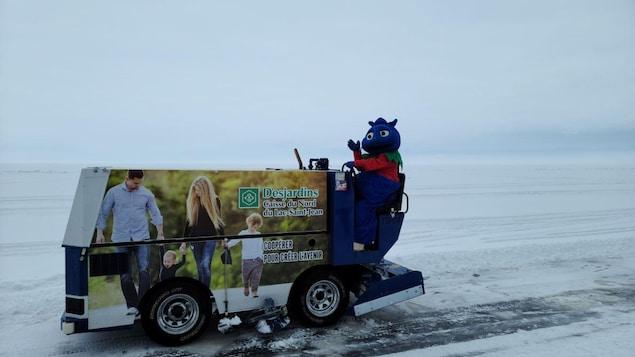 Une mascotte sur une Zamboni sur un lac gelé.