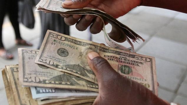 Des mains tiennent des billets de banque américains.